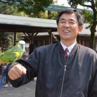 Star attraction: A Blue-fronted Amazon parrot named Tiffany perches on the arm of Toshihisa Deguchi, head of Miyazaki City Phoenix Zoo, on March 10. | KYODO