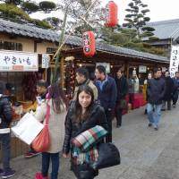 Beckoning: Travel agency officials and others from Shanghai stroll past shops and restaurants at the entrance to Ise Jingu Shrine in Ise, Mie Prefecture, in late February. | CHUNICHI SHIMBUN