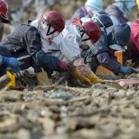 Ongoing:  Workers sort debris left by the March 2011 quake-tsunami in Higashimatsushima, Miyagi Prefecture, on April 11. | KYODO