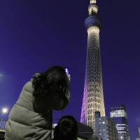 One and counting: A woman takes a picture of Tokyo Skytree on Tuesday night as her son looks on. The 634-meter tower, which opened last May 22, will be lit up until June 4 in 12 different patterns to celebrate the anniversary. | KYODO