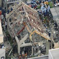 Aftermath: Police and firefighters inspect the remains of what was the Shiespa annex in Tokyo's Shibuya district after a deadly blast destroyed the spa in June 2007, killing three people. | KYODO