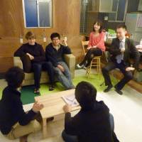 Roommates: Students from the United States and South Korea chat recently with a Japanese office worker in a 'share house' in Chiyoda Ward, Tokyo. | KYODO