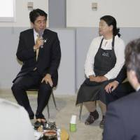 In the field: Prime Minister Shinzo Abe talks with farmers in tsunami-hit areas in Sendai on Sunday. Abe said that the Tokyo Metropolitan Assembly election in June will be a litmus test for his government ahead of the Upper House election in July. | KYODO