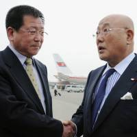 Making contact: Isao Iijima (right), an adviser to Prime Minister Shinzo Abe, is greeted by Kim Chol Ho, vice director of the North Korean Foreign Ministry's Asian Affairs Department, upon his arrival Tuesday at Pyongyang airport. | KYODO