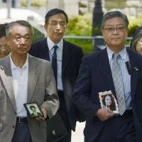 Sasago suit: Bereaved parents who filed a lawsuit against Central Nippon Expressway Co. walk to the Yokohama District Court on Wednesday. | KYODO