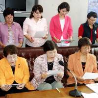 Pushback: Masako Ishimine (center), the head of a women's group in Okinawa, reads out a statement of protest targeting Osaka Mayor Toru Hashimoto on Wednesday in Naha. | KYODO