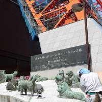 New home: A construction worker removes the statues of the Sakhalin huskies that accompanied the first Japanese Antarctic expedition team, in the late 1950s, from the base of Tokyo Tower on Wednesday. | KYODO