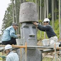 Like a rock: Workers install a stone Moai statue replica from Chile Thursday in Minamisanriku, Miyagi Prefecture. | KYODO