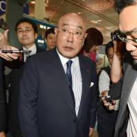 Operative snared: Isao Iijima, Prime Minister Shinzo Abe's campaign guru, is surrounded by the media Saturday at Beijing international airport while returning to Tokyo from North Korea. | KYODO
