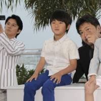 Winning kudos: Director Hirokazu Koreeda (pointing) poses with actors (from left) Masaharu Fukuyama, Shogen Whang and Keita Ninomiya during a photo call for the film 'Like Father, Like Son' at the Cannes Film Festival on Saturday. | AP
