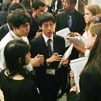 Give and take: A Japanese student (center), playing the role of a diplomat, negotiates with other students during a mock U.N. meeting Saturday in New York. | KYODO