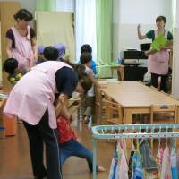 School's in: Teachers speak with children Friday at a nursery school that recently opened in Yokohama's Minami Ward. | KYODO