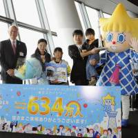 Number's up: Hiroshi Komine, his wife, Naomi, their daughter, Arisa, 5, and son Seiya, 5, pose Monday with Michiaki Suzuki, president of Tobu Tower Skytree Co., after the family accounted for the 6.34 millionth visitor to the observation deck of the 634-meter broadcasting tower, which will mark its first anniversary Wednesday. | KYODO