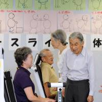Respect for the aged: Emperor Akihito and Empress Michiko visit a nursing home in Wako, Saitama Prefecture, last September. | KYODO