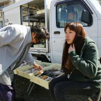Needed service: An elderly woman checks out food items sold by Mao Higashi, sitting outside her truck during a stop in a village outside Kihoku, Mie Prefecture, on March 14. | KYODO