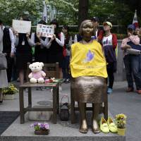 Emotive issue: Students gather around a statue symbolizing a wartime sex slave during an anti-Japan rally in front of the Japanese Embassy in Seoul on Wednesday to demand an official apology and compensation from Tokyo. | AP