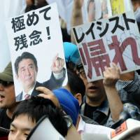 People against hate speech toward Korean residents hold signs saying 'Go Home Racists' and 'Very Unfortunate' with a picture of Prime Minister Shinzo Abe. | SATOKO KAWASAKI
