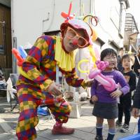 Serving up smiles: Ichiro Oishi, a volunteer clown who has been traveling across the disaster-hit regions to help cheer up tsunami survivors, stands in front of his ramen shop in Kawagoe, Saitama Prefecture, last February. | KYODO