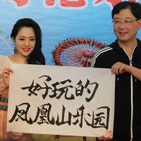 Brushwork: Porn actress Sola Aoi displays her calligraphy while taking part in a promotional event at a theme park in Ningbo, China, on April 14. | AFP-JIJI
