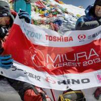 Mission accomplished: Yuichiro Miura (left) and his son, Gota, pose for a photo with a flag after reaching the summit of Mount Everest on Thursday. | MIURA DOLPHINES CO./AP