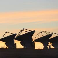 Eye toward the sky: Some of the dish antennas that make up the ALMA radio telescope are seen in silhouette in March on Chile's Atacama Plateau, at an altitude of around 5,000 meters. | KYODO
