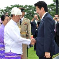 Hand in hand: Myanmar President Thein Sein greets Prime Minister Shinzo Abe at the Presidential Palace in Naypyitaw on Sunday. | AP