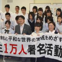 A million strong: Nagasaki Mayor Tomihisa Taue holds up a banner with high school students who are aiming to collect 1 million signatures calling for the abolition of nuclear weapons at the Nagasaki Atomic Bomb Museum on Sunday. | KYODO