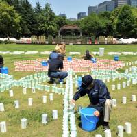 Happy 110th: Organizers of 'Hibiya Akari Terrace,' one of the main events to mark the 110th anniversary of Tokyo's Hibiya Park this weekend, prepare candles on Friday. | YOSHIAKI MIURA