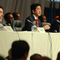 On point: Prime Minister Shinzo Abe speaks at a special session on Somalia during the fifth Tokyo International Conference on Africa Development in Yokohama on Friday as Somalia's president, Hassan Sheikh Mohamud (right), looks on. | POOL
