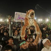 Roar deal: Supporters of former Pakistani Prime Minister Nawaz Sharif listen to him delivering a speech during an election campaign rally in Lahore, Pakistan, on Thursday. | AP