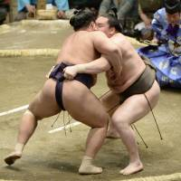Summer breeze: Hakuho (right) gets to grips with Tochiozan on the first day of the Summer Grand Sumo Tournament on Sunday. | KYODO