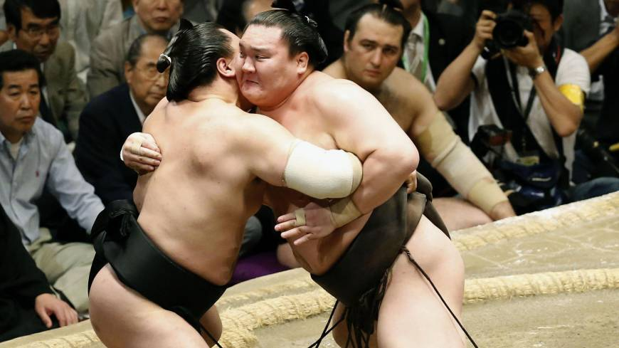 Perfect example: Hakuho (right) tussles with Harumafuji on his way to victory with a flawless record at the Summer Grand Sumo Tournament on Sunday.