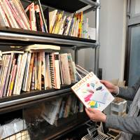 Whatever you want: A worker at  bunbougu in central Tokyo shows off a book featuring stationery items at the cafe in April. The shelves at the theme cafe, in Shibuya Ward, are filled with other books and magazines dedicated to stationery.   | YOSHIAKI MIURA