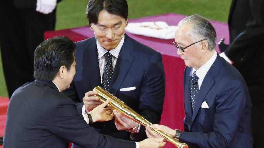Special recognition: Prime Minister Shinzo Abe presents Hideki Matsui (center) and Shigeo Nagashima (right) a commemorative gold bat as part of their People's Honor Award ceremony on Sunday before the Yomiuri Giants-Hiroshima Carp game at Tokyo Dome.