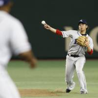 One to forget: Seibu shortstop Hideto Asamura makes an errant throw in the 10th inning to hand the Yomiuri Giants a 2-1 win over the Lions on Saturday. | KYODO