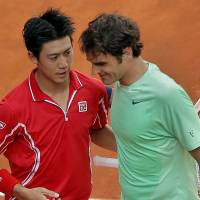 Win to remember: Kei Nishikori hugs Roger Federer after beating the 17-time Grand Slam champion in the third round of the Madrid Open on Thursday. Nishikori won 6-4, 1-6, 6-2. | AP