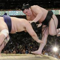 Low blow: Myogiryu (left) shoves Harumafuji out of the ring at the Summer Grand Sumo Tournament on Monday. | KYODO