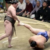 Simply the best: Hakuho overpowers Okinoumi on Friday at the Summer Grand Sumo Tournament. | KYODO