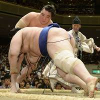No margin for error: Harumafuji (rear) takes down Aoiyama at the Summer Grand Sumo Tournament on Saturday. | KYODO