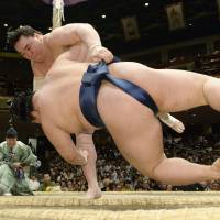 Crash landing: Harumafuji (rear) throws Goeido at the Summer Grand Sumo Tournament on Monday. | KYODO