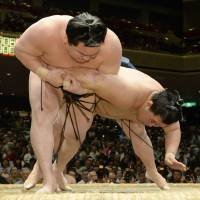 Impressive strength: Yokozuna Hakuho (left) outduels Goeido on Tuesday at the Summer Grand Sumo Tournament. | KYODO