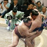 Never a dull moment: Ozeki Kisenosato sends Karuryu out of the raised ring with a loss at the Summer Grand Sum Tournament on Friday. | KYODO