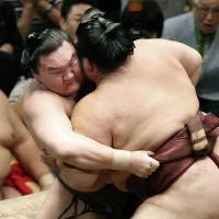 In the heat of the moment: Yokozuna Hakuho (left) grapples with Kisenosato at Ryogoku Kokugikan on Saturday. Hakuho improved to 14-0 by beating the ozeki at the Summer Grand Sumo Tournament. | KYODO