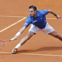 Slide and reach: Switzerland's Stanislas Wawrinka plays a shot from Portugal's Gastao Elias in their quarterfinal match at the Portugal Open on Friday. Wawrinka won 6-4, 6-4 to advance to the semifinals. | AP