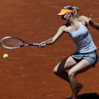 No walkover: Maria Sharapova plays a shot from Romania's Alexandra Dulgheru in their first-round match at the Madrid Open on Monday. Sharapova won 7-5, 6-2. | AFP-JIJI