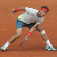 Tough on clay: Rafael Nadal plays a shot from France's Benoit Paire in their second-round match at the Madrid Open on Wednesday. Nadal won 6-3, 6-4. | AP