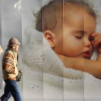 Modern parenting: An elderly couple in Tokyo walk past an advertisement displaying a picture of a baby. Today's parents pay big money for devices and information in the search for help in putting their little darlings to sleep. | BLOOMBERG