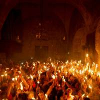 Holy fire: Orthodox Christians hold up candles in the Church of the Holy Sepulcher in Jerusalem on Saturday. | AFP-JIJI