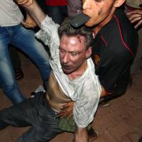 Too late: Libyan civilians help injured U.S. Ambassador to Libya Chris Stevens at the U.S. Consulate compound in Benghazi in the early hours of last Sept. 12 following an overnight attack on the building. | AFP-JIJI