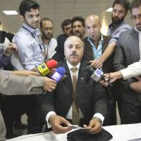 Throwing his name into a packed ring: Former Iranian lawmaker Ghasem Shole Sadi is surrounded by reporters in  Tehran on  Tuesday as he registers his candidacy for the upcoming presidential election. | AP